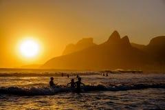 Unidentifiable konturer som tycker om solstrålar för sen eftermiddag på Ipanema, sätter på land royaltyfri bild