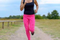 Unidentifiable löpare med att jogga för rosa färgflåsanden royaltyfri bild