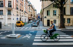 Unidentifiable man cycling down the street. The public bike system in Paris royalty free stock photography