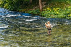 Unidentifiable man fishing at Jezernica river, Bohinj Lake Stock Images