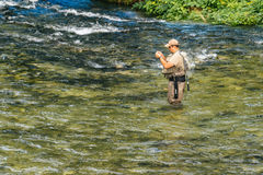 Unidentifiable man fishing at Jezernica river, Bohinj Lake Stock Image