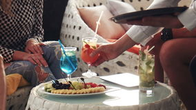 Unidentifiable people drinking and eating at table. Unidentifiable people being served alcoholic beverages and eating appetizers at table stock video footage