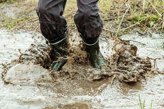 Unidentifiable person jumping in muddy water. Close up on stop motion of unidentifiable pair of feet in boots jumping and splashing in muddy puddle of water Stock Photos
