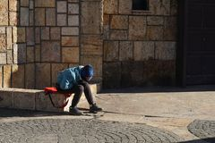 Unidentifiable poor child sits alone, sad and desperate. Unidentifiable, poor child sits alone and sad on the street on a cold day. Depression signs in an royalty free stock photography