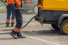 Unidentifiable road maintenance workers repairing driveway Royalty Free Stock Image