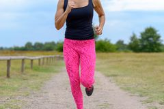 Unidentifiable runner with pink pants jogging. Unidentifiable female runner with pink pants jogging along empty gravel road next to open green field in a close royalty free stock image