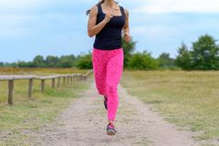 Unidentifiable runner with pink pants jogging. Unidentifiable female runner with pink pants jogging along empty gravel road next to open green field royalty free stock photo