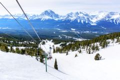 Skiers on Chairlift Up a Ski Slope in the Canadian Rockies royalty free stock photo
