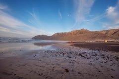 Unidentifiable surfare i berömda Famara sätter på land i Lanzarote, kanariefågelöar, Spanien arkivfoton