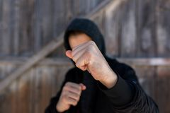 Unidentifiable teenage boy attacking with hes bare hands, focus on the fist. Conceptual image of juvenile delinquency royalty free stock photography