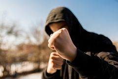 Unidentifiable teenage boy attacking with hes bare hands, focus on the fist. Conceptual image of juvenile delinquency stock photo