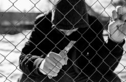 Unidentifiable teenage boy behind wired fence holding a paper knife at correctional institute, focus on the fence in black and whi. Te, conceptual image of royalty free stock photo