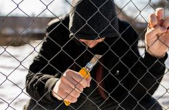 Unidentifiable teenage boy behind wired fence holding a paper knife at correctional institute. Focus on the fence, conceptual image of juvenile delinquency royalty free stock images