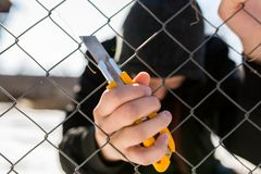 Unidentifiable teenage boy behind wired fence holding a paperknife at correctional institute. Unidentifiable teenage boy behind wired fence holding a paper knife stock image