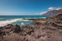 Unidentifiable turist- simning i kustlinjelandskap i den Puerto Santiago, Tenerife, Spanien royaltyfri fotografi