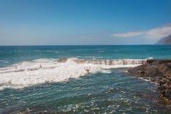Unidentifiable turist- simning i kustlinjelandskap i den Puerto Santiago, Tenerife, Spanien royaltyfria bilder