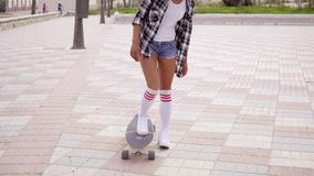 Unidentifiable woman stepping on skateboard stock video