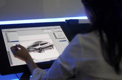 An unidentified artist showcases a digital sketchi. KUALA LUMPUR, MALAYSIA - DEC 3: An unidentified artist showcases a digital sketching of a concept car during Stock Photos