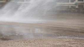 Unidentified asian worker using a powerful hose sprayer from a tanker truck to wash the road stock footage