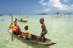 Unidentified Bajau family paddle a dug out boat in sunny day. The Bajau tribe are the sea gypsies who are nomads and live in the sea. Children do not attend royalty free stock photos