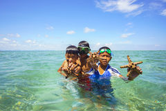 Unidentified Bajau Laut kids on a boat in Maiga Island Stock Photos