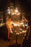 Unidentified balinese men light candles before a traditional Kecak Fire Dance ceremony in Hindu temple. Stock Image