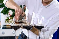 Unidentified barman pouring liquid in martini glass. Unidentified barman pouring liquid in a martini glass Stock Image