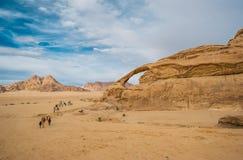 Unidentified bedouins with a caravan of camels walks in the desert of Wadi Rum stock image