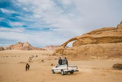 Unidentified bedouins with a caravan of camels walks in the desert of Wadi Rum royalty free stock images