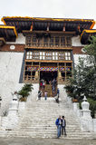 Unidentified buddhist monks and vistors with traditional robes are entering and leaving the Punakha Dzong monastery, Punakha, Bhut Stock Image