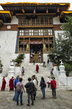 Unidentified buddhist monks and vistors with traditional robes are entering and leaving the Punakha Dzong monastery, Punakha, Bhut Royalty Free Stock Photography