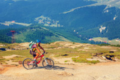 Unidentified biker climbs the hill in Bucegi Mountains in Romania Royalty Free Stock Image