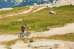 Unidentified biker climbs the hill in Bucegi Mountains in Romania Royalty Free Stock Photography