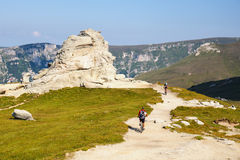 Unidentified biker climbs the hill in Bucegi Mountains in Romania Stock Photo