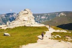 Unidentified biker climbs the hill in Bucegi Mountains in Romania Stock Photo
