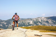 Unidentified biker climbs the hill in Bucegi Mountains in Romania Royalty Free Stock Photo