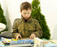 Unidentified boy carefully reads books at children showcase Royalty Free Stock Image