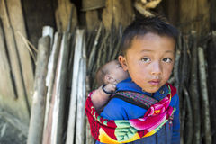 An unidentified boy carrying his young sibling on his back at home Stock Photo