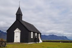 Unidentified bride and groom standing in front of Famous black church,Iceland. Royalty Free Stock Photos