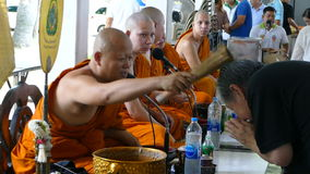 Unidentified Buddhist monk sprinkles holy water on visitors stock footage