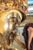 Unidentified Burmese monk is cleaning Buddha statue with the golden paper at Mahamuni Buddha temple, August Royalty Free Stock Image