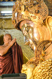 Unidentified Burmese monk is cleaning Buddha statue with the golden paper at Mahamuni Buddha temple, August Royalty Free Stock Photo