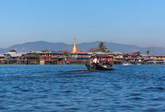 Unidentified Burmese are ridind the Longtail boat which have pagoda and traditional house background Royalty Free Stock Photos