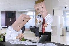 Unidentified businessman scolding his employee. Picture of unidentified businessman scolding his employee by using a megaphone in the office Royalty Free Stock Image
