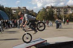 Unidentified byker. SLAVIANSK, UKRAINE - SEPTEMBER 11, 2011: Unidentified byker performs a trick on a bicycle at the city festival in Slaviansk on September Royalty Free Stock Photography
