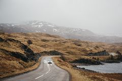 Unidentified car driving on a road going through Scottish Highlands near Lochinver, Scotland. Unidentified car driving on a road going through Scottish stock images
