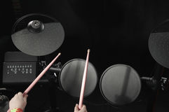 Unidentified Caucasian little girl play electronic drum. Top view. Stock Photos