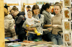Unidentified child and happy young mother making choice at the book festival Stock Photography