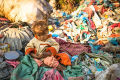 Unidentified child is sitting while her parents are working on dump, Dec 22, 2013 in Kathmandu, Nepal Stock Photo