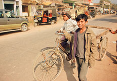 Unidentified children driving on bicycle cart through dirt indian street in India Stock Photography